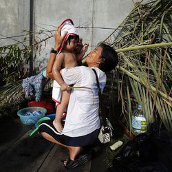 Mildred Villaflores, a member of the Ormoc 2nd Ward, bathes her son Arthur King Villaflores at the chapel, Tuesday, Nov. 19, 2013, following Typhoon Haiyan in the Philippines.