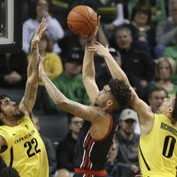 Oregon's Addison Patterson, left, and Will Richardson, right, pressure Utah's Timmy Allen during the first half of an NCAA college basketball game in Eugene, Ore., Sunday, Feb. 16, 2020.
