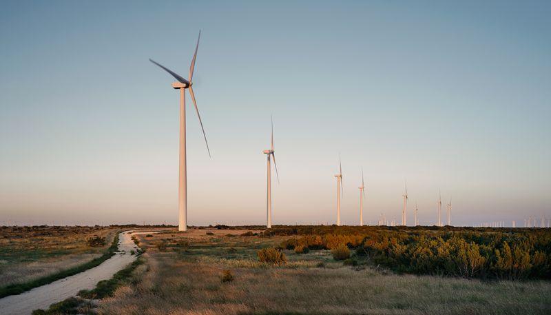 Seven windmills in a row amidst a grassy field.