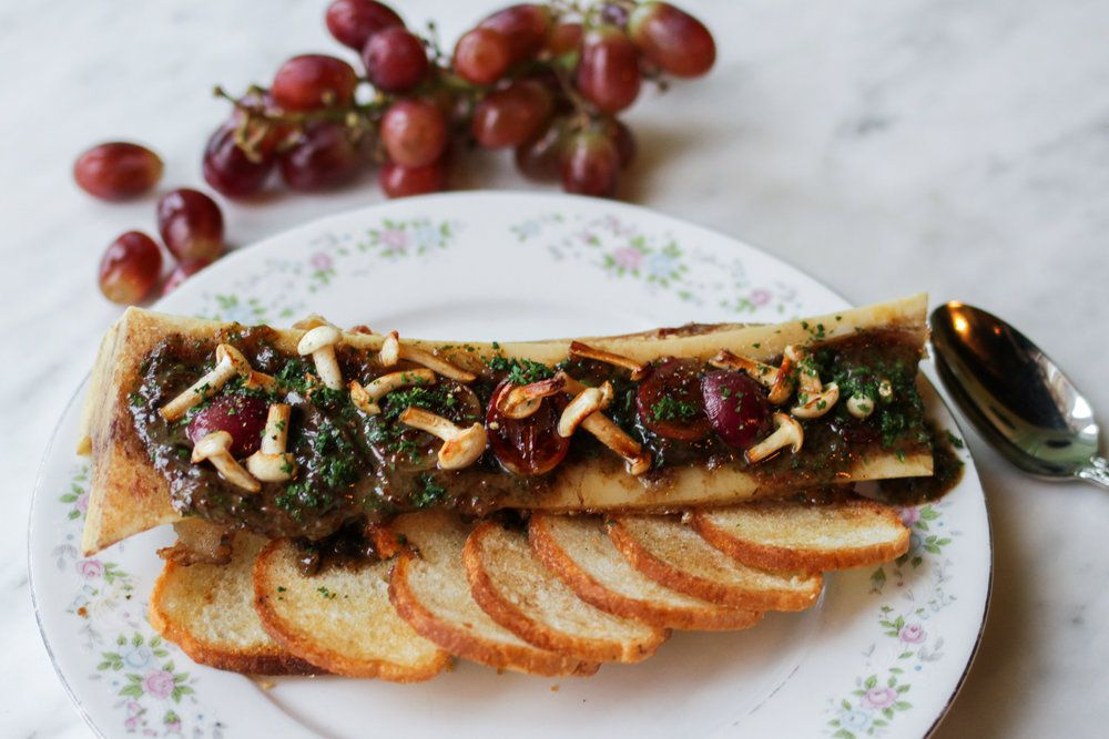 A plate of roasted bone marrow with bread chips.