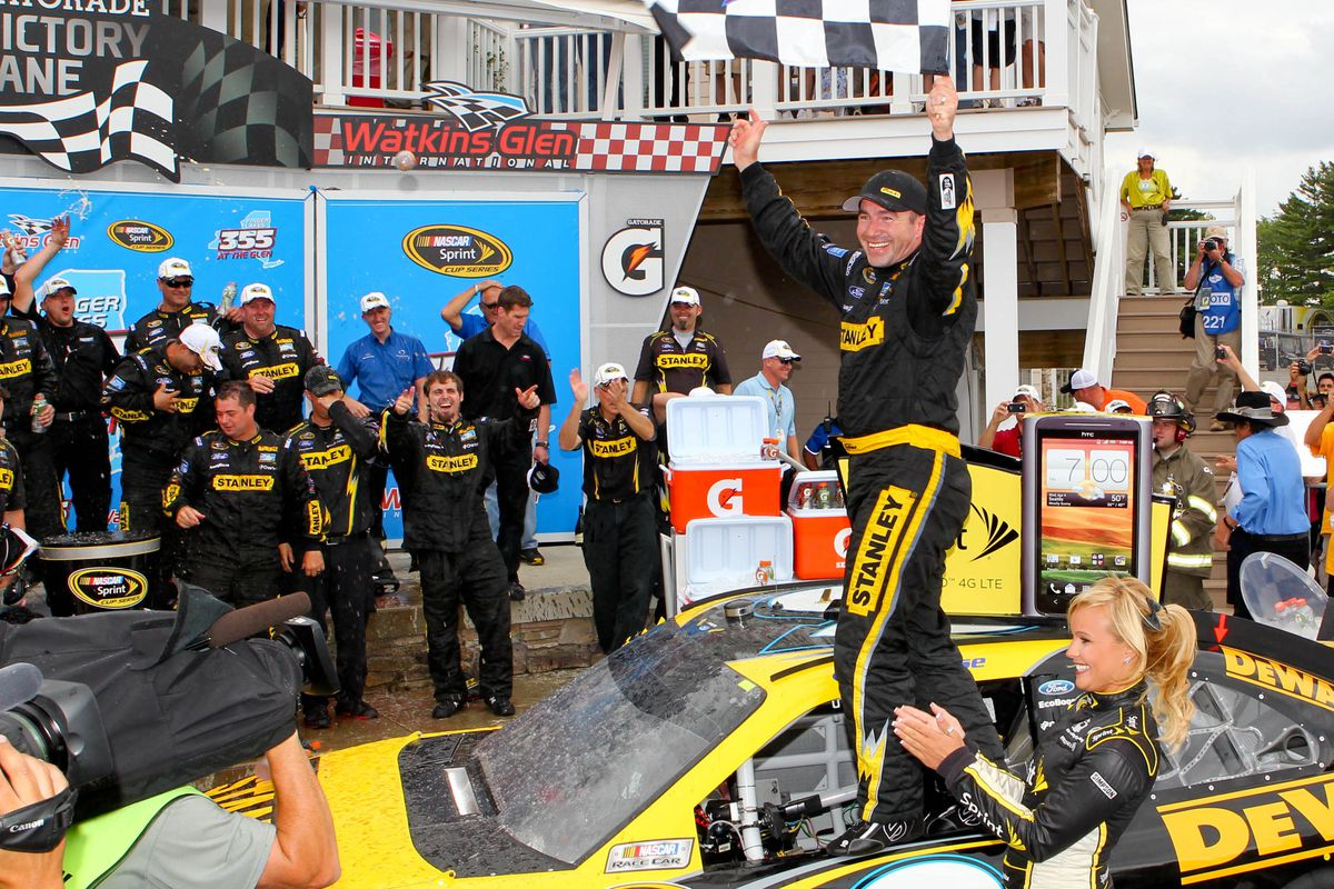 Aug 12, 2012; Watkins Glen, NY, USA; Sprint Cup Series driver Marcos Ambrose (9) celebrates a win in victory circle following the Finger Lakes 335 at The Glen at Watkins Glen International.  Mandatory Credit: Timothy T. Ludwig-US PRESSWIRE