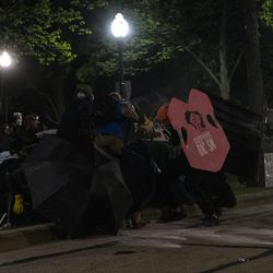 Protesters try to form a shield wall as police shoot them with pepper balls during a protest over the shooting of Jacob Blake outside the Kenosha County Courthouse, Tuesday, Aug. 25, 2020, in Kenosha, Wis.