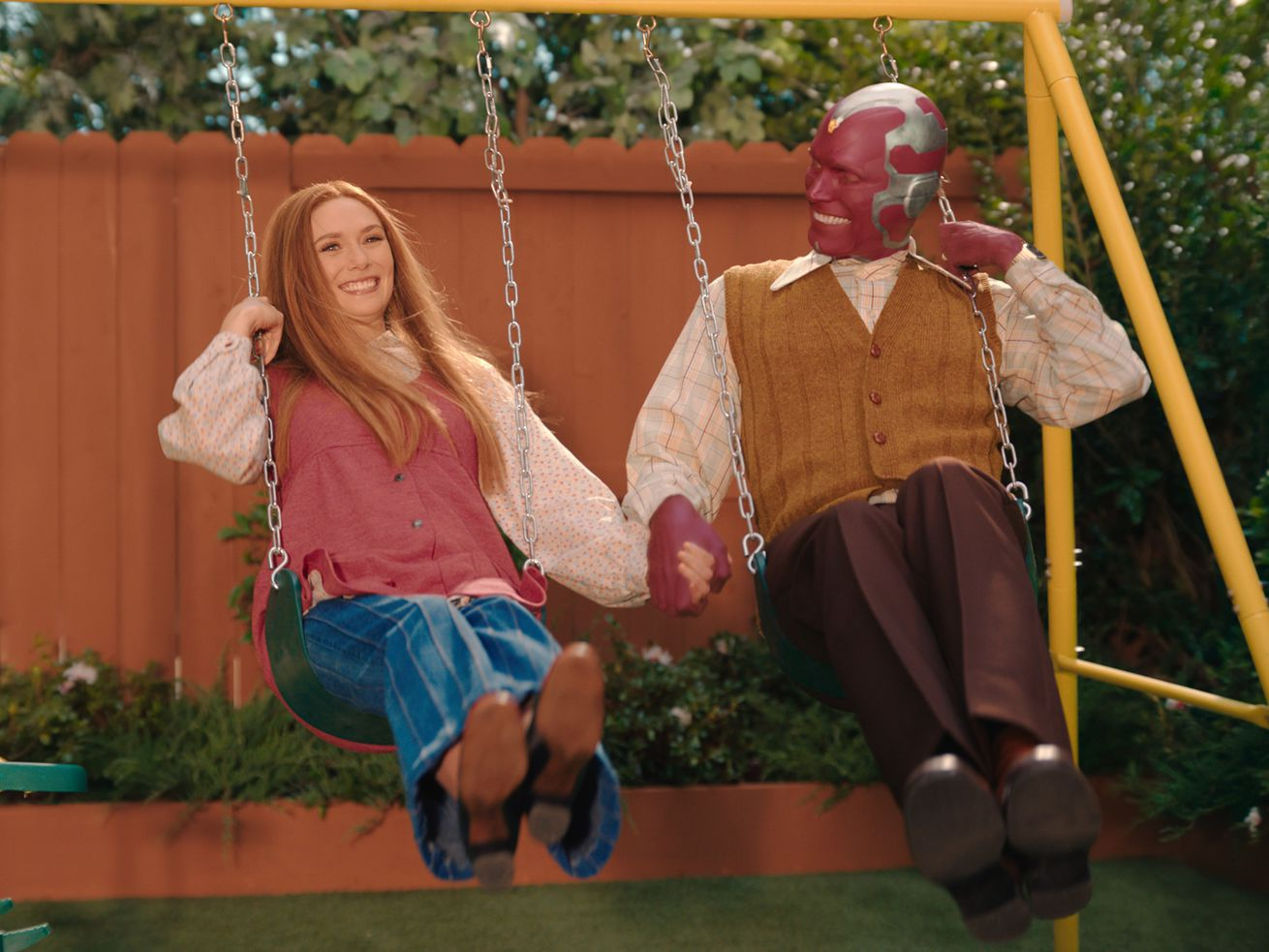 Wanda and Vision hold hands while swinging on a swing set.