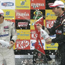IndyCar driver Will Power, of Australia, right, celebrates his victory with third place winner Takuma Sato, of Japan, at the IndyCar Sao Paulo 300 winner's podium, in Sao Paulo, Brazil, Sunday, April 29, 2012.