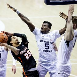 Pacific Tigers guard Justin Moore (25) goes to the hoop against Brigham Young Cougars forward Gideon George (5) and forward Matt Haarms (3) at the Marriott Center in Provo on Saturday, Jan. 30, 2021.