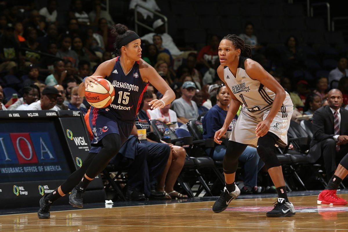 Natasha Cloud of the Washington Mystics dribbles the ball against Monique Currie of the San Antonio Stars.