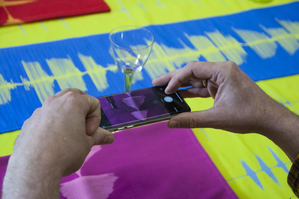 A person is holding a smartphone over a table with red, blue, and green textiles woven with the patterns of sound waves