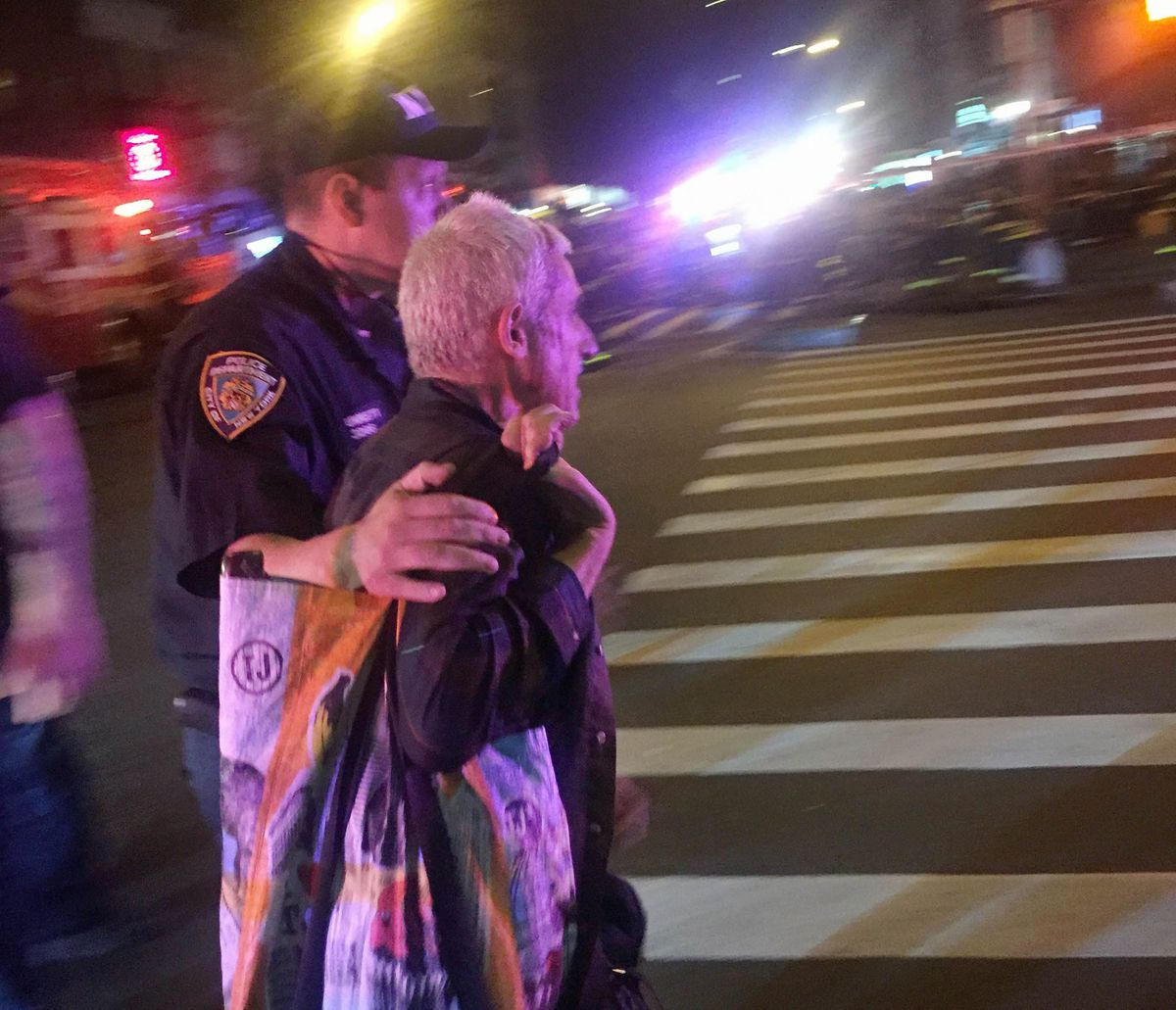 A police officer escorts an injured man from the scene of a possible explosion on West 23rd Street in New York. | AP photo