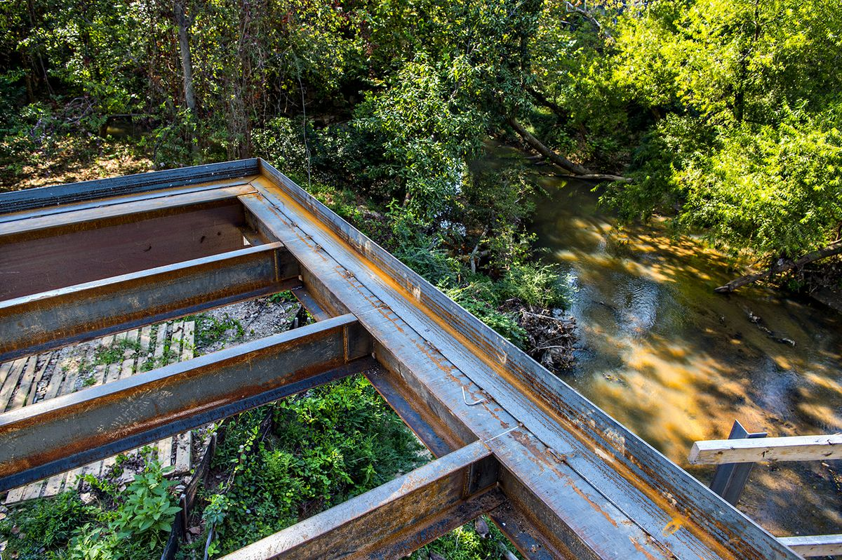 A bridge section of steel that stretches over a creek.