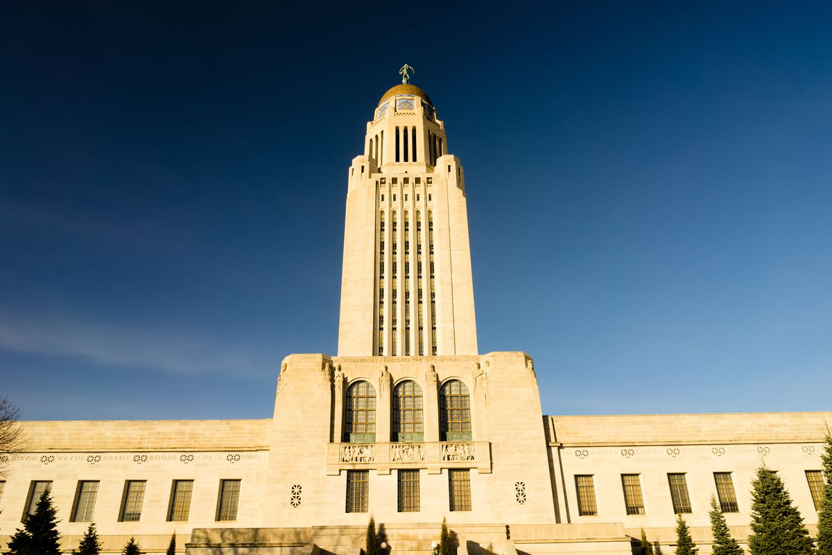 The exterior of the Nebraska State Capitol. The facade is tan. There is a tall tower.