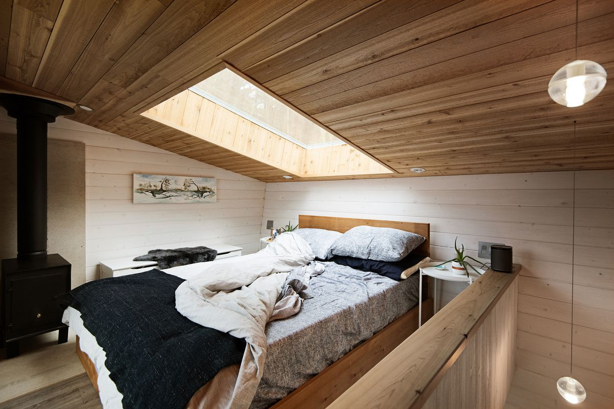Lofted bedroom has wooden ceilings and a skylight above. A wood-burning stove sits in the corner.