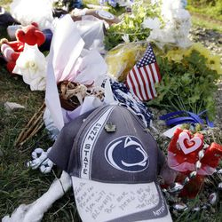 In this Friday, April 20, 2012, photo, Penn State hats, flowers and footballs decorate the gravesite of former Penn State football coach Joe Paterno in State College, Pa. No apparent images of the late Paterno were shown on the Beaver Stadium video screens for Saturday's Blue-White game. But the Hall of Fame coach remains an endearing figure to Penn State fans, from the blue and white carnations left at the Paterno statue outside the stadium to a 5K race run Sunday in his name.