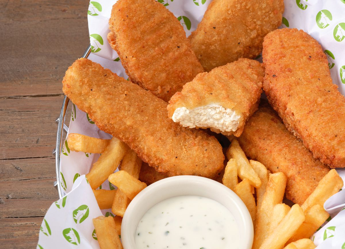 Fried plant-based chicken tenders in a basket with french fries and ranch dip.