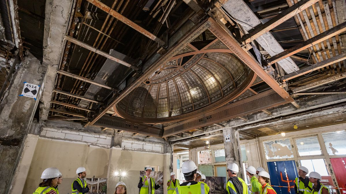 A group of people in hardhats and yellow vests stand in the center of a gutted room. Above them is a large oval leaded-glass skylight.
