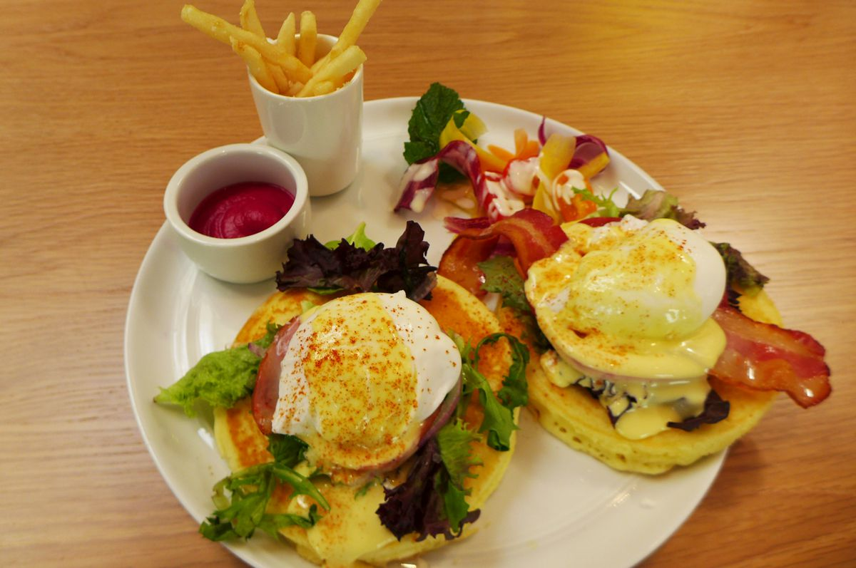 Two poached eggs on top of pancakes with salad in between.