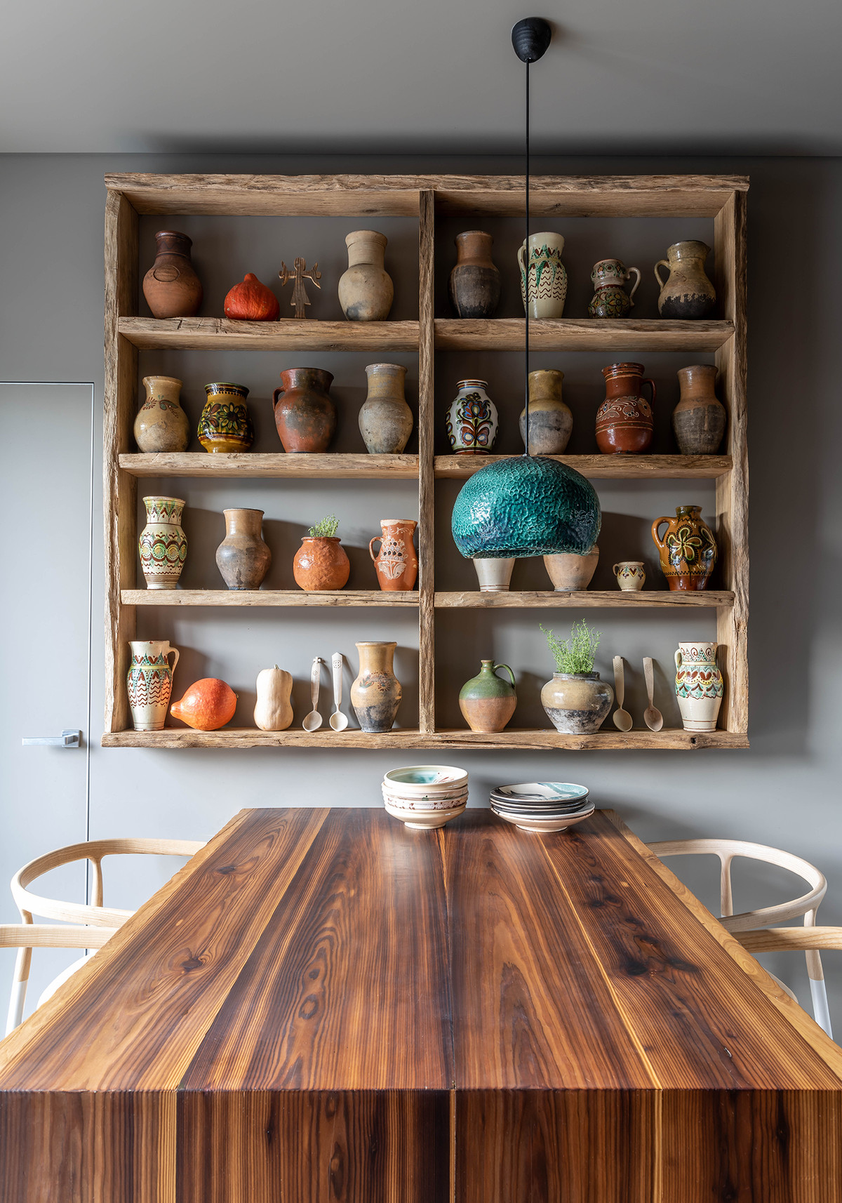 Dining table next to ceramics mounted on shelf.