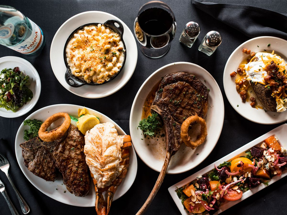 A table full of steaks and sides.