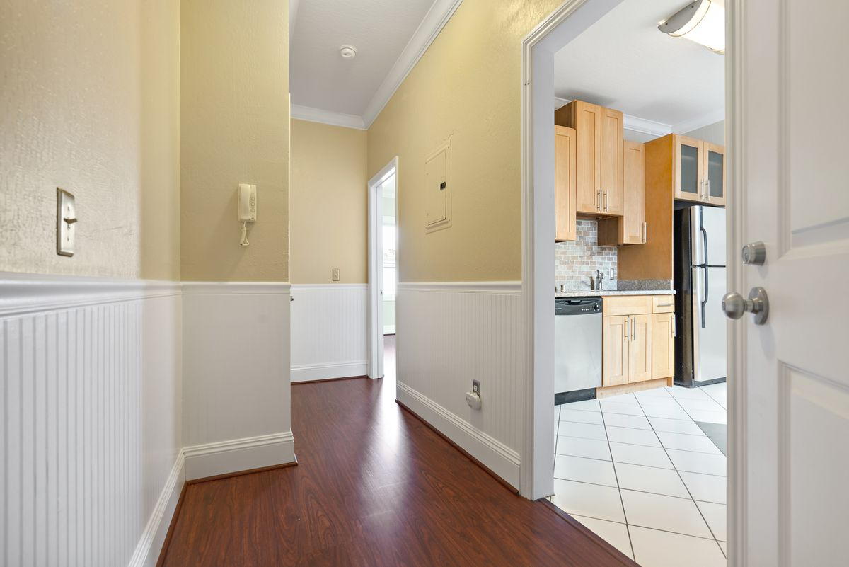 A hallway with wooden floors and a door open leading to a kitchen.