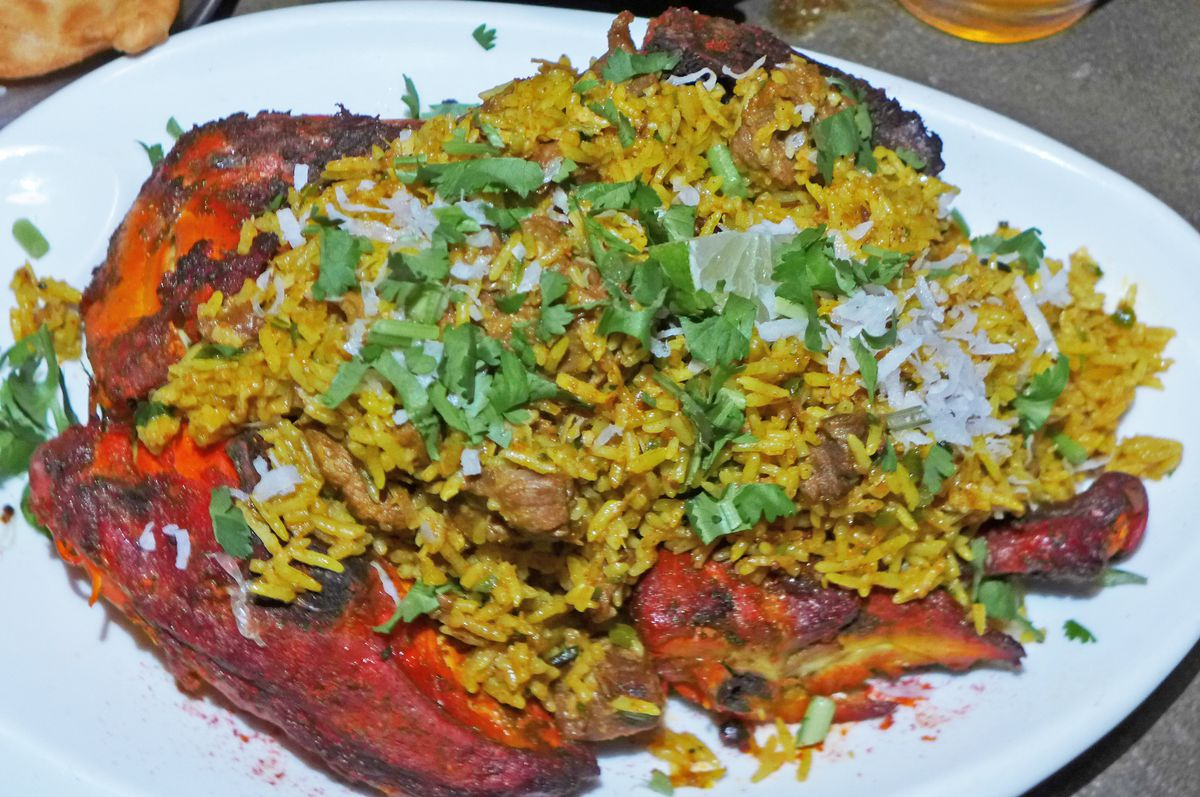 Bright red chicken pieces cradling brown rice studded with chunks of browner meat.