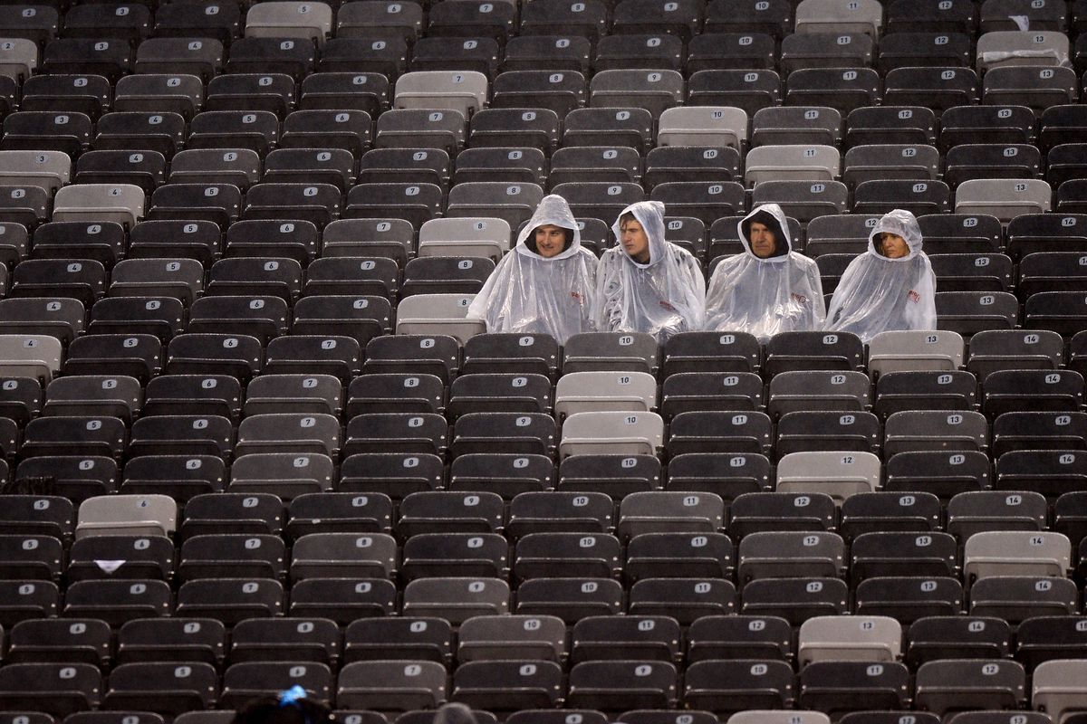 Solitary fans sit in the rain during the second half
