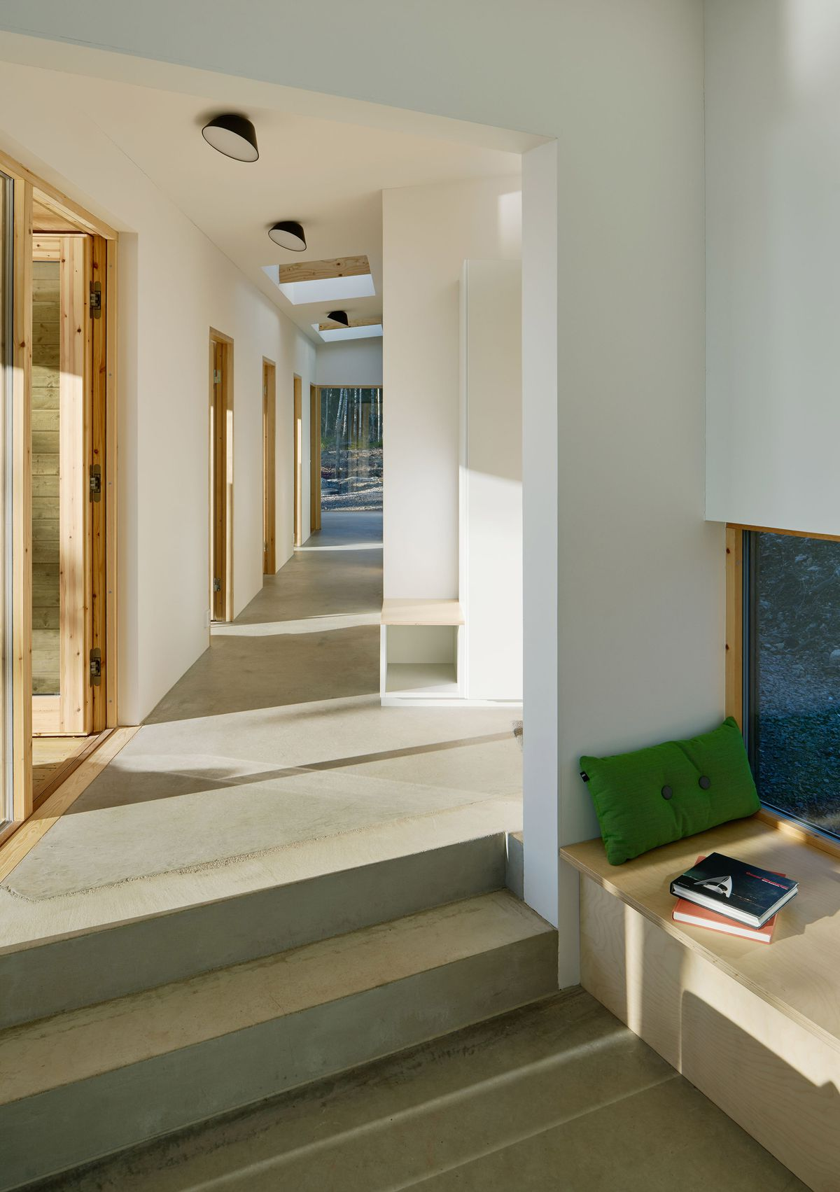Concrete hallway next to built-in seating nook