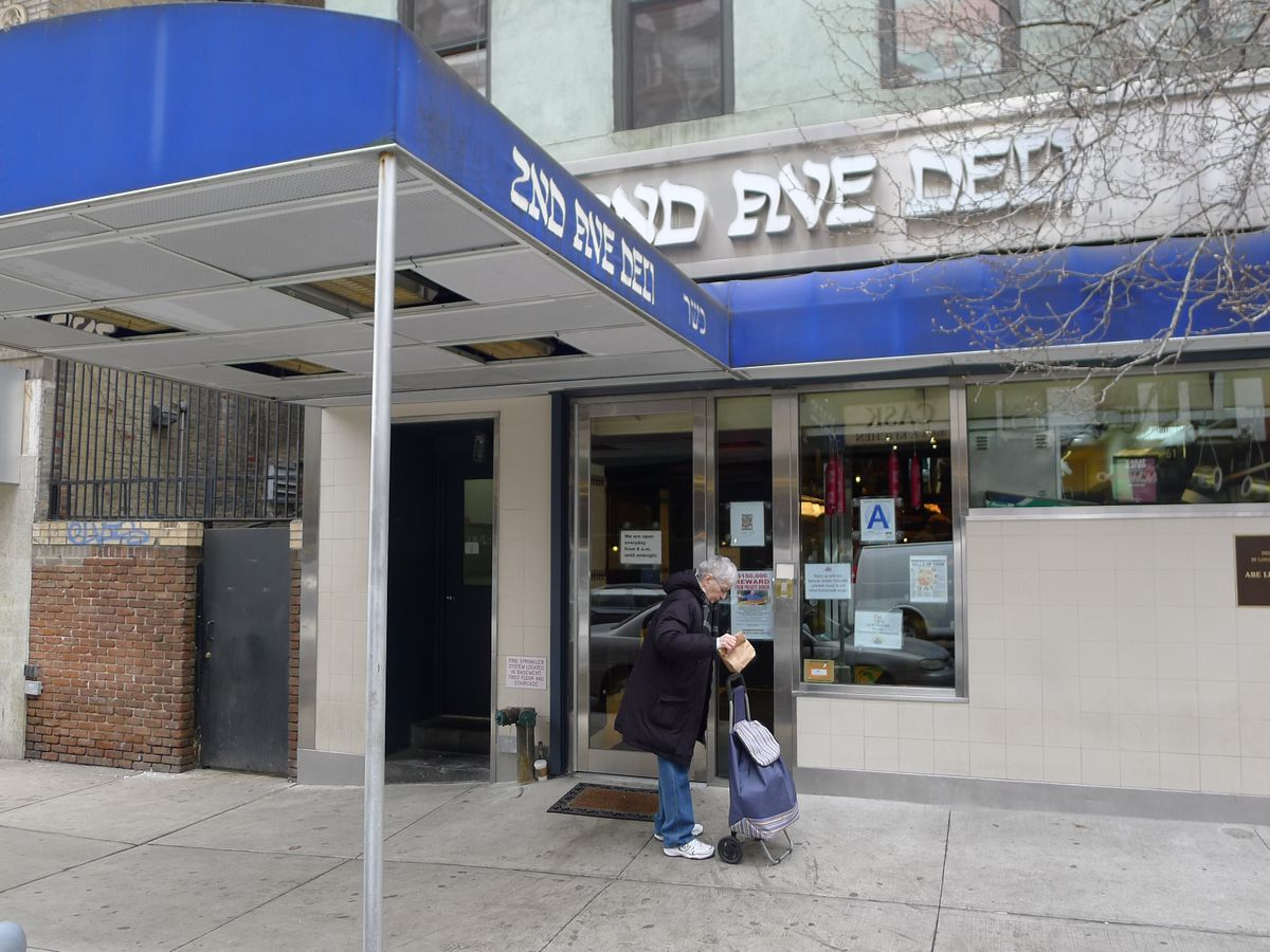 """A woman stands under a blue awning with the words: """"2nd Ave Deli"""""""