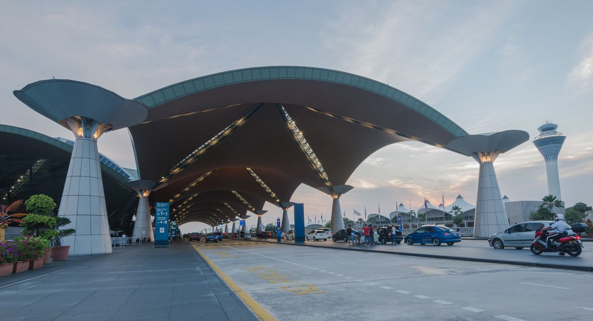 The exterior of Kuala Lumpur International Airport. There is a curved roof with columns.
