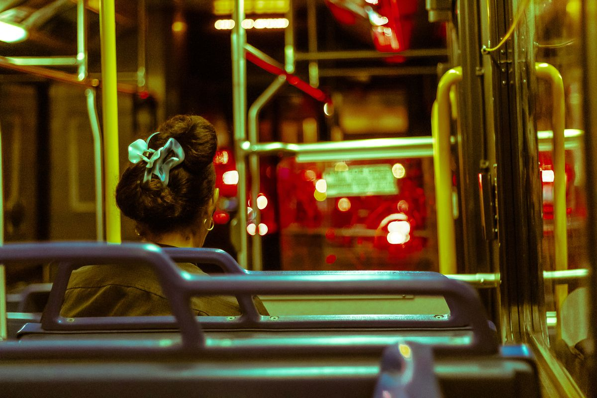 A women rides a bus alone late at night