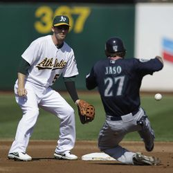 Seattle Mariners' John Jaso (27) steals past Oakland Athletics shortstop Stephen Drew, left, in the second inning of a baseball game Saturday, Sept. 29, 2012, in Oakland, Calif.