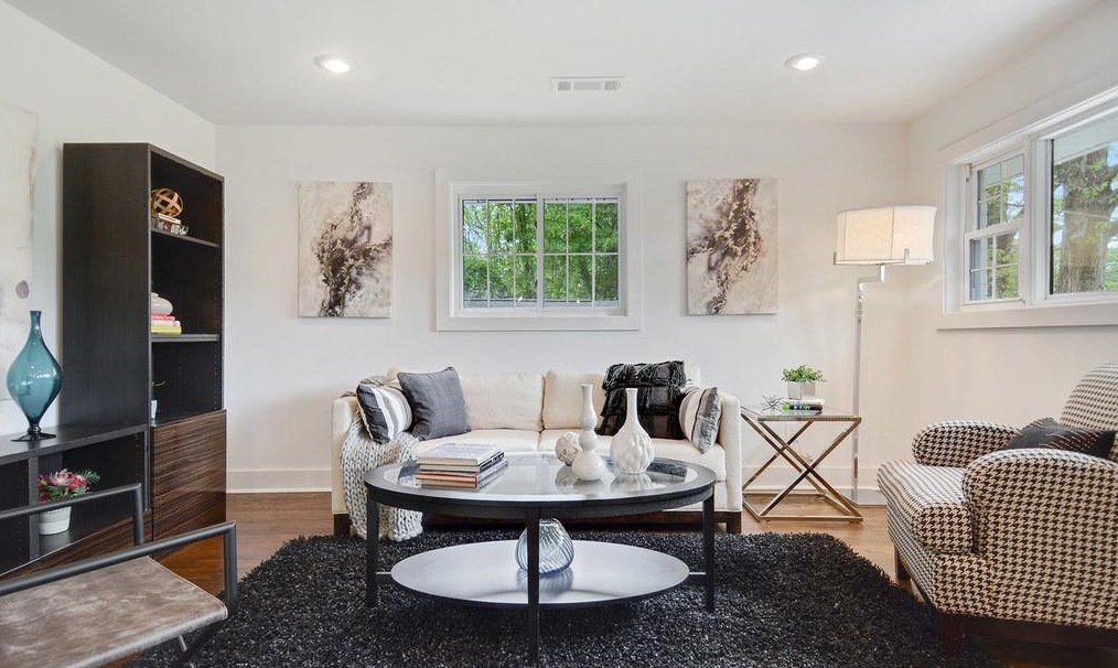 A white little living room with a white couch and two chairs.