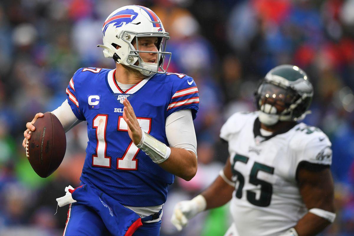 Buffalo Bills quarterback Josh Allen runs with the ball as Philadelphia Eagles defensive end Brandon Graham defends during the third quarter at New Era Field.