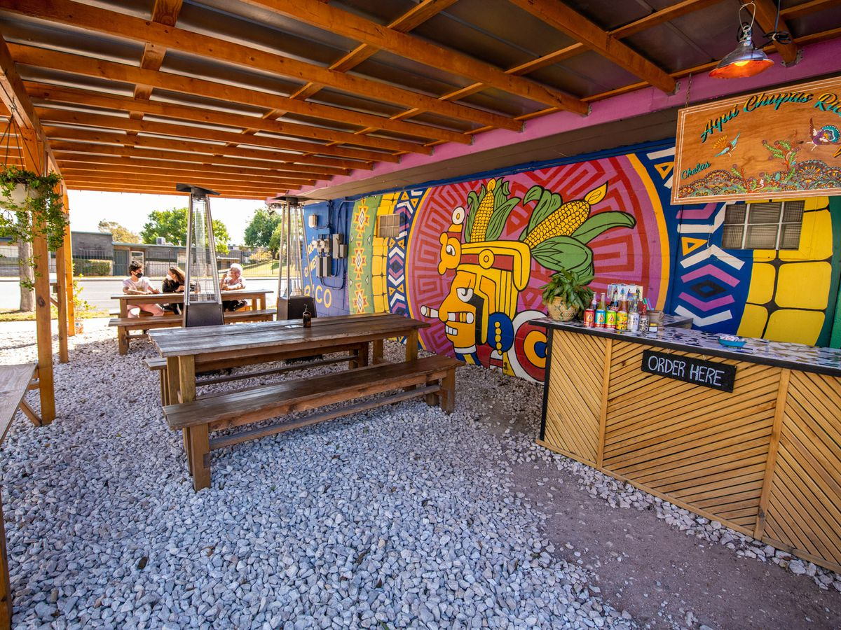 An outdoor patio with gravel flooring and wooden awning and wood picnic tables in front of a brightly colorful moural and an outdoor wooden bar