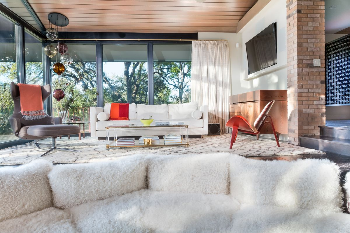 Midcentury modern interior shot from conversation pit with fluffy white pillows looking toward big walls of windows