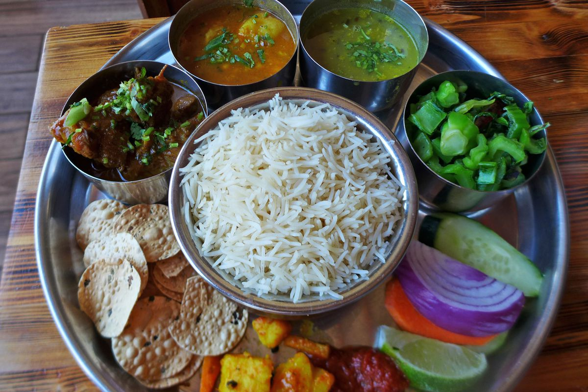 The goat thali at Sumnima offers a mountain of basmati rice and many side dishes.