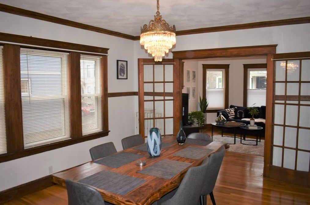 A spacious dining room with a table and chairs, and the room opens onto another room through double doors.
