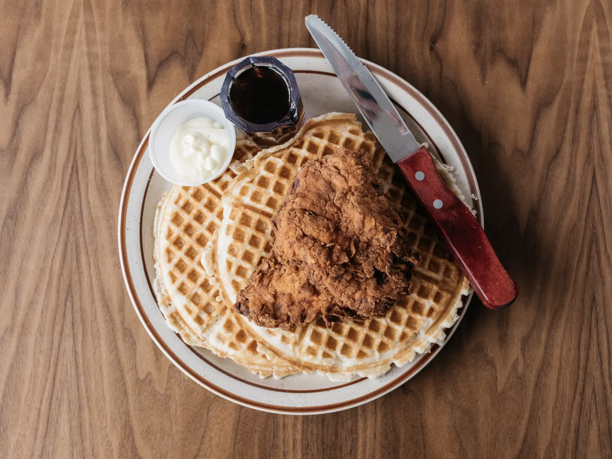 A top-down view of a plate of fried chicken and waffles.