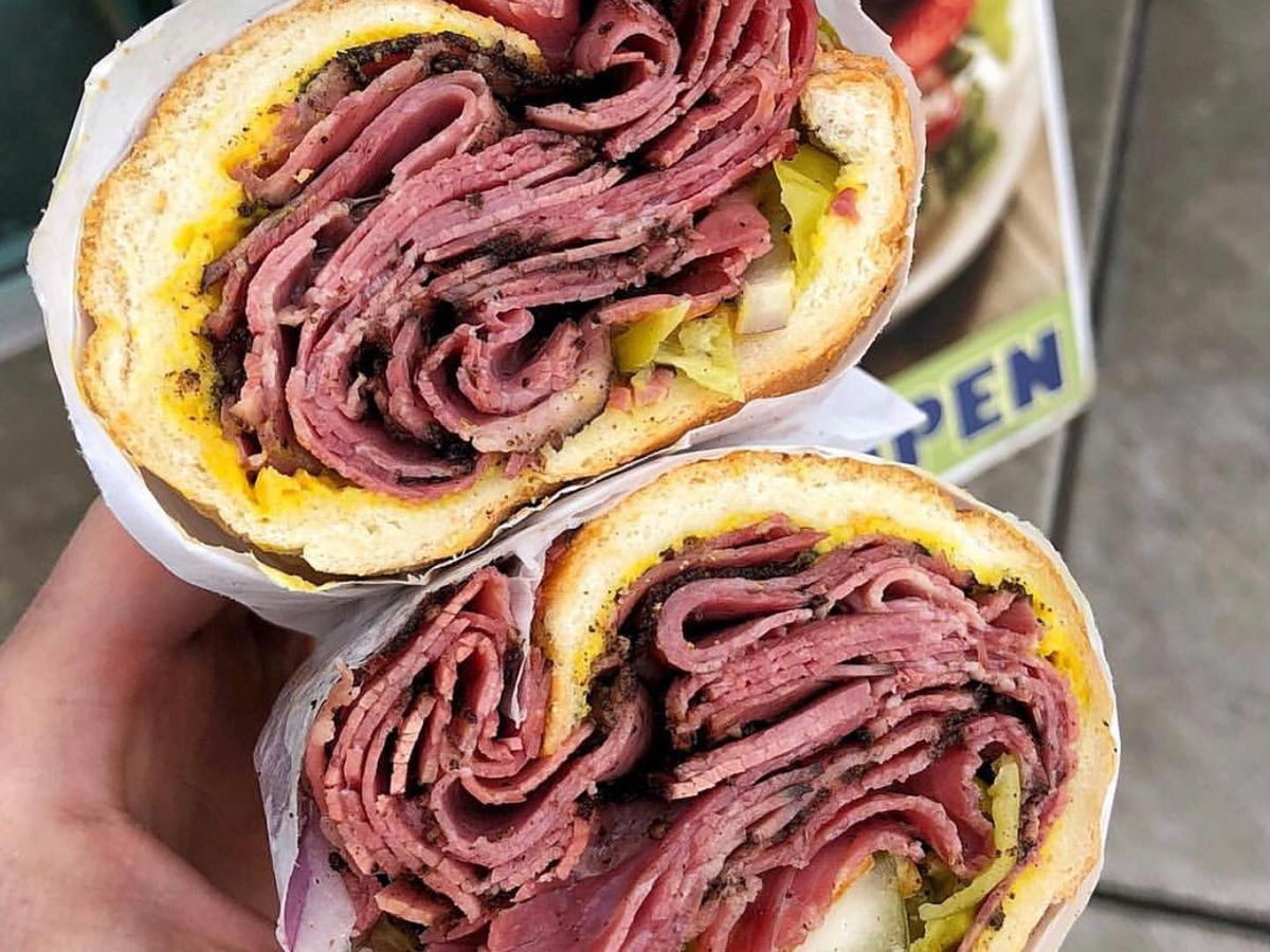 A pastrami sandwich cut in half and stacked