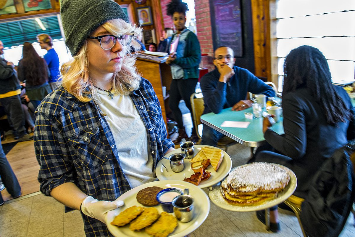 Daisy Alexander (center) carries plates of freshly made breakfast to a table at Home grown off of Memorial Drive.