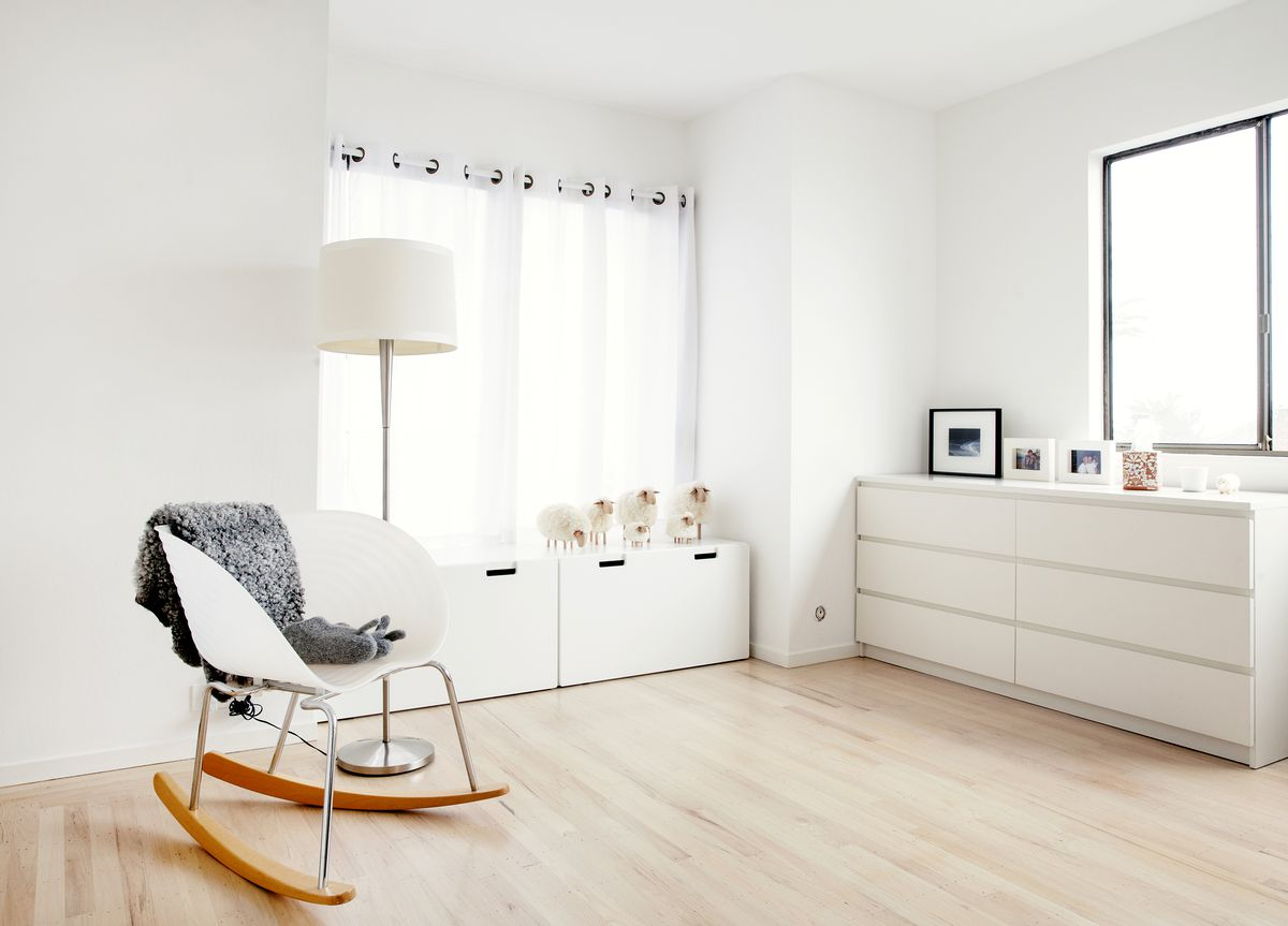 A white chair and white dresses in an all white bedroom.