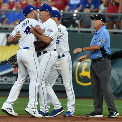Danny Duffy is restrained arguing with umpire Tom Hallion after being ejected.
