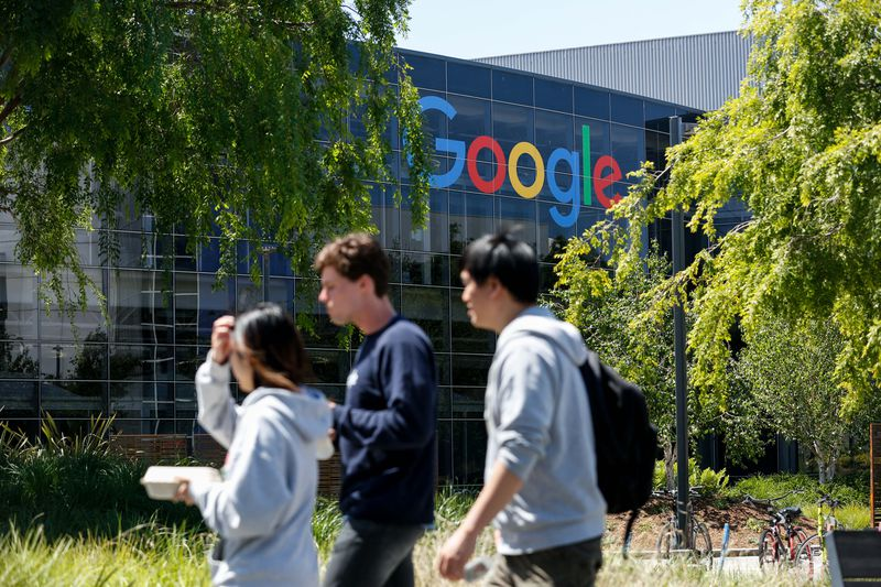 Three young people walk in front of the Google headquarters in Mountain View, California.
