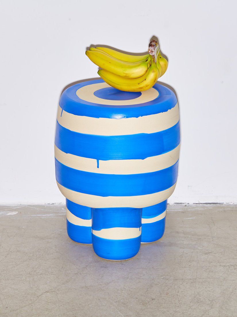 A bunch of bananas sit on top of a white-and-blue striped stool.