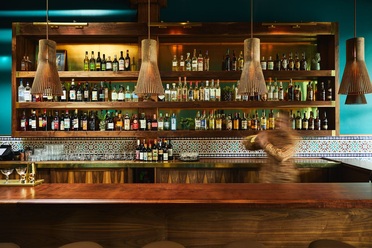 A view of a bar with the back lined with colorful bottles and bartender mixing a drink in the foreground, blurry.