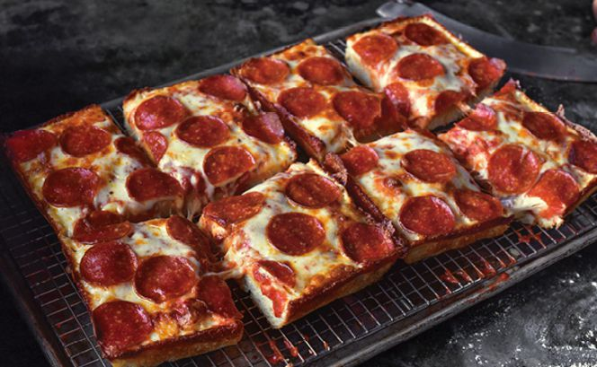 A rectangular pepperoni pizza is cut up into squares and rests on a wire rack in a pan