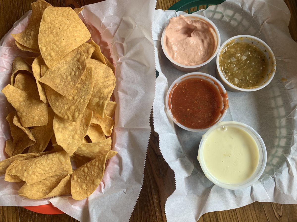 chips in a red basket, trio of salsas and queso