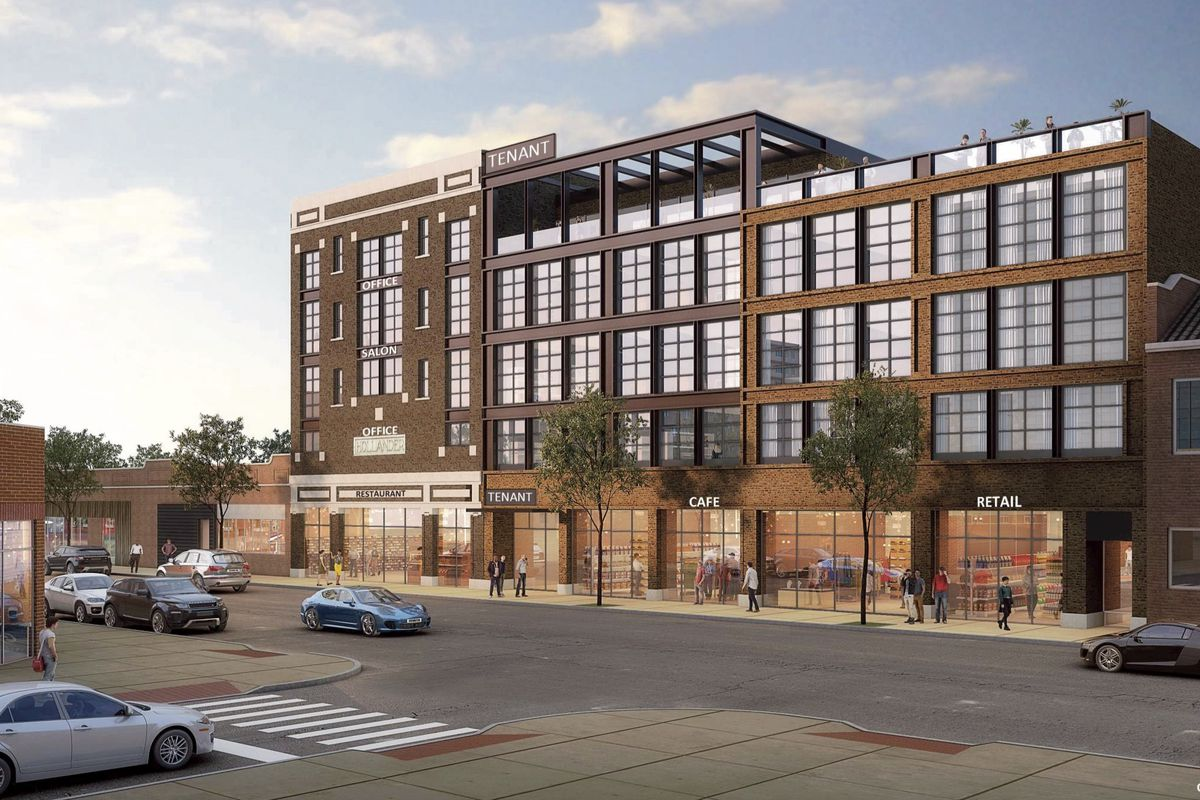 A brick five-story building with ground floor retail topped by industrial style warehouse windows and a roof deck.