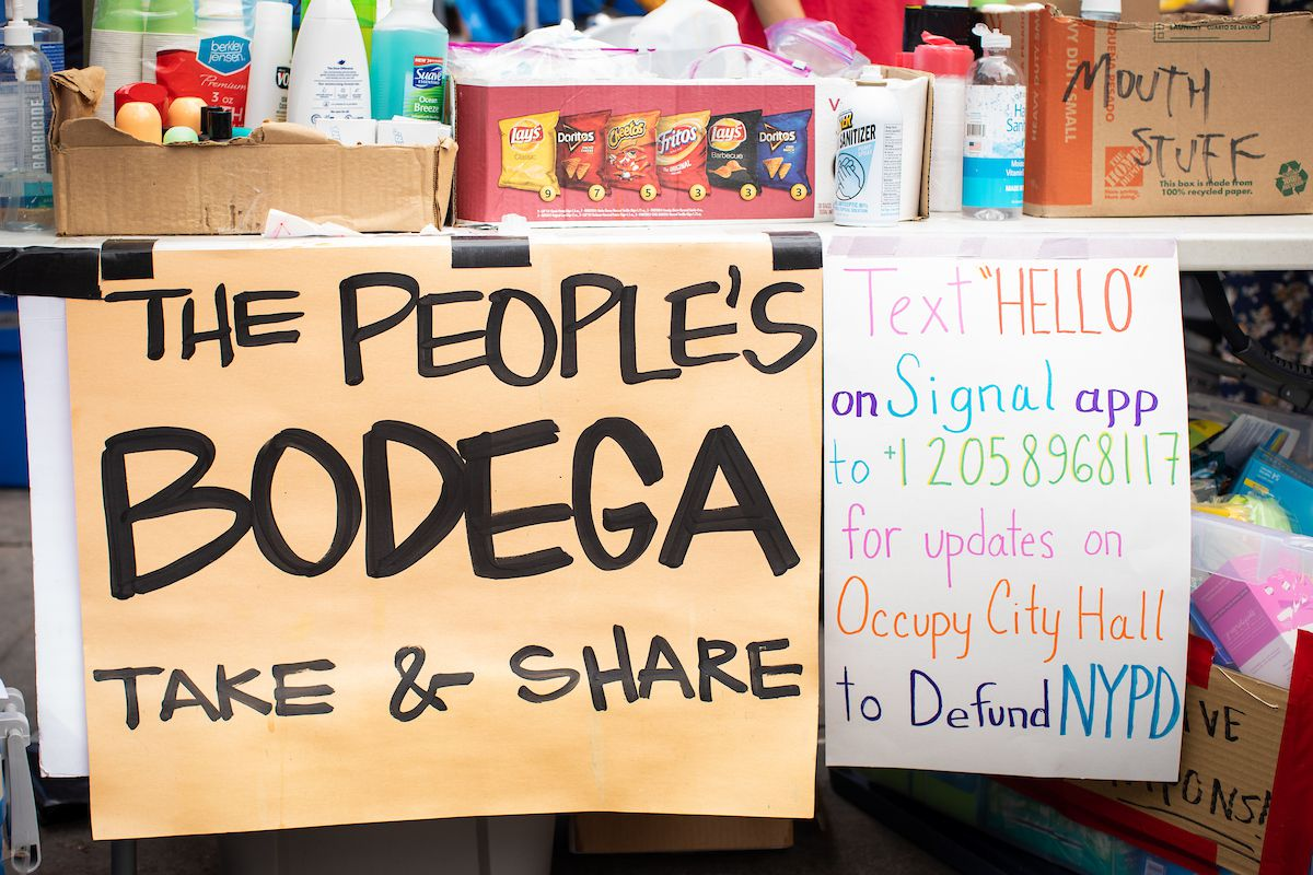 "Two handmade signs hang from a makeshift snack table. One reads ""The people's bodega take & share"" in all capital letters, while the other urges people to text a phone number for updates"