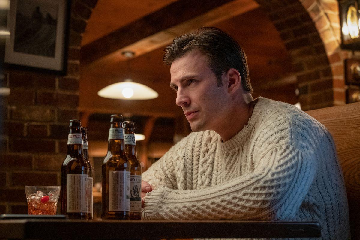 Chris Evans se sienta en un suéter con los brazos cruzados sobre una mesa con dos cervezas a su lado en Knives Out