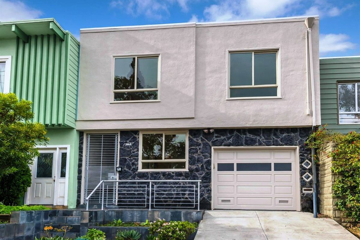 The facade of 228 Holladay Avenue, a flat-roofed modern home with a stone garage.
