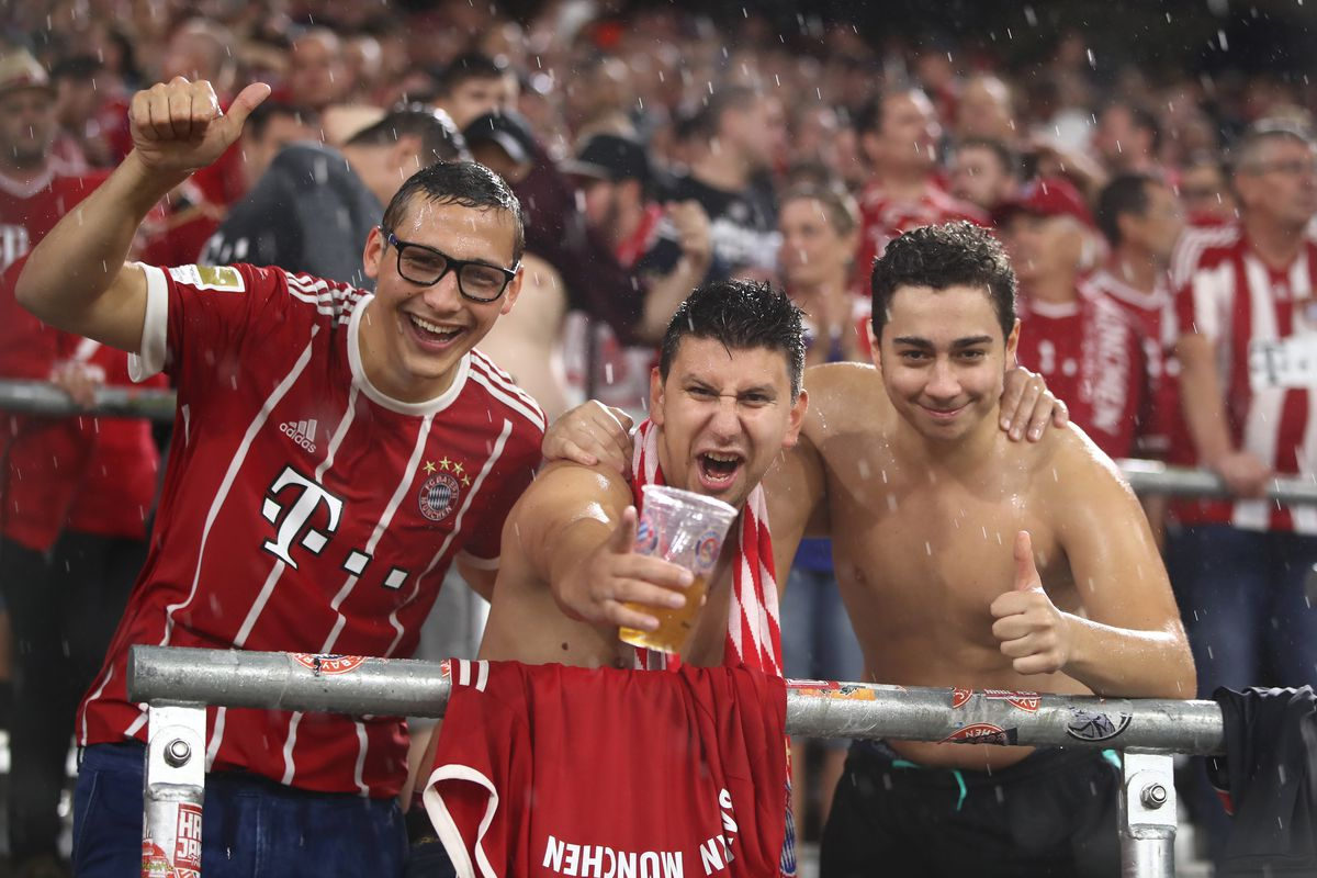 MUNICH, GERMANY - AUGUST 18: Fans celebrate even in the rain and bad weather during the Bundesliga match between FC Bayern Muenchen and Bayer 04 Leverkusen at Allianz Arena on August 18, 2017 in Munich, Germany.
